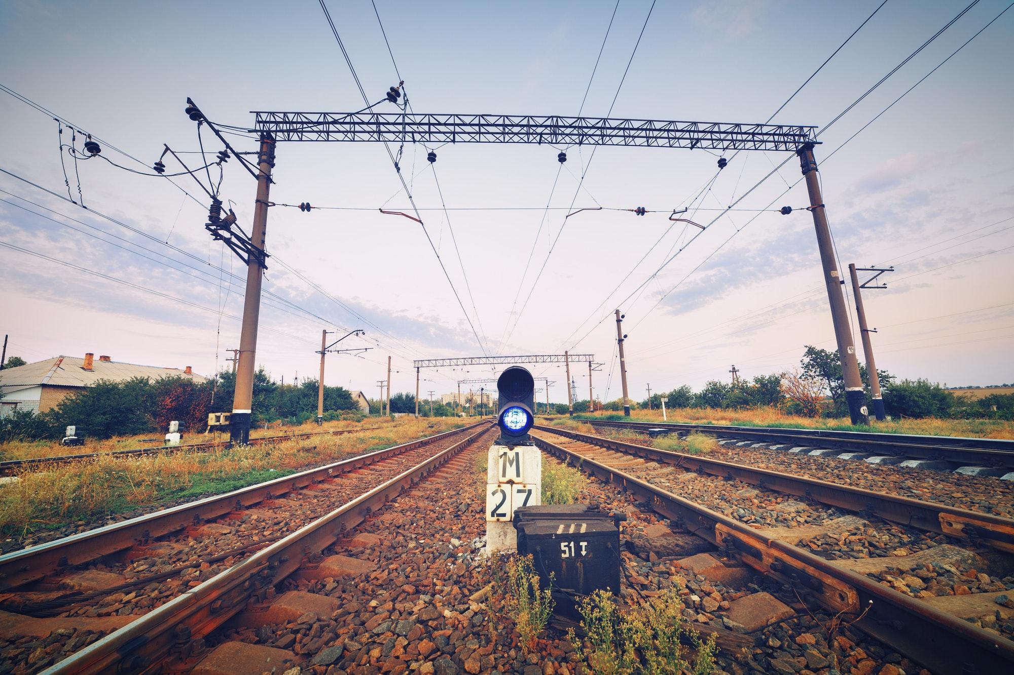 Train platform and traffic light at sunset. Railroad. Railway st
